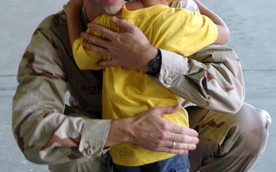 Lt. Col. Douglas Dickerson says goodbye to his son before boarding a plane for the Middle East.