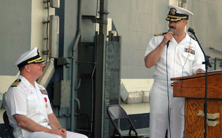 Carrier Air Wing 5 commander Capt. Michael P. McNellis, right, talks to former commander Capt. Garry R. Mace in his remarks during their change of command ceremony Sept. 2 aboard the USS Kitty Hawk off Laem Chabang, Thailand.