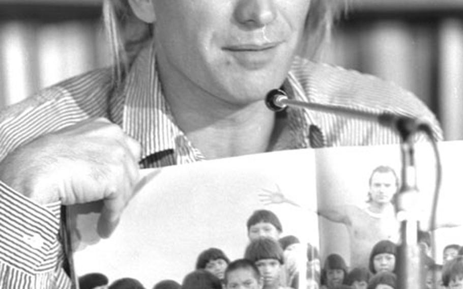 Sting holds up a photo of Brazilian children during a May, 1989 press conference in Tokyo.