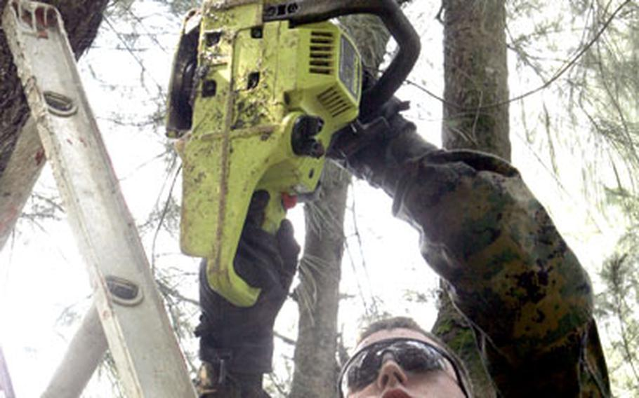 Lance Cpl. David Wilkie saws a branch off a tree at the Nakijin Christian Church Camp on Wednesday.