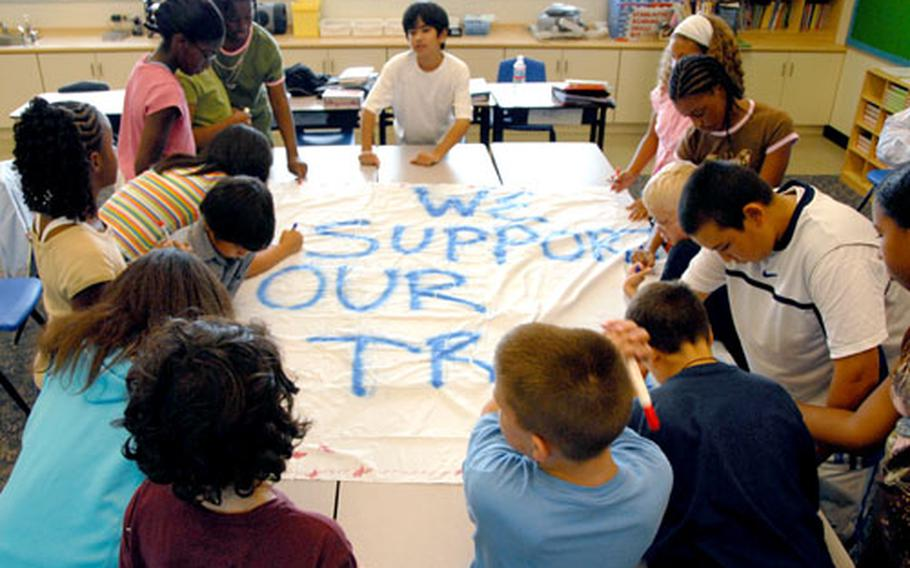 Sixth graders at Kinser Elementary School decorate a banner with stars, flags and their names. After participating in the Freedom Walk on Monday, the class will hang its banner in tribute to the U.S. troops and in remembrance of those who died in the Sept. 11, 2001 terrorist attacks.