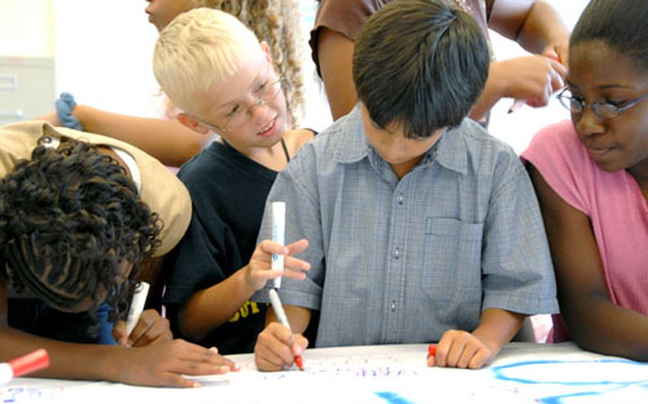 Cameron Toal, left, Vandrick Cruz, center, and Chyryssandra Tatum sign their names and draw pictures on the banner.