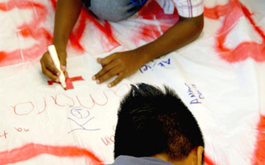 "Camara Rawls, 10, top, and Run Asato, 11, decorate a banner that says ""We Remember."""