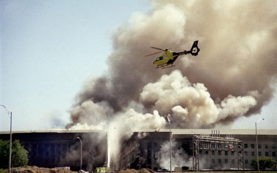 A helicopter flies over the Pentagon on Sept. 11, 2001, after terrorists crashed a hijacked airliner into the building.
