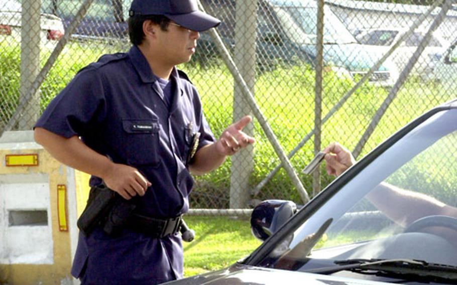 Japanese Master Labor Contract gate guard Yoshinao Yamashiro checks the identification of a driver at the Legion Gate on Camp Foster last year. Prior to Sept. 11, 2001, Japanese guards on Marine bases were unarmed.