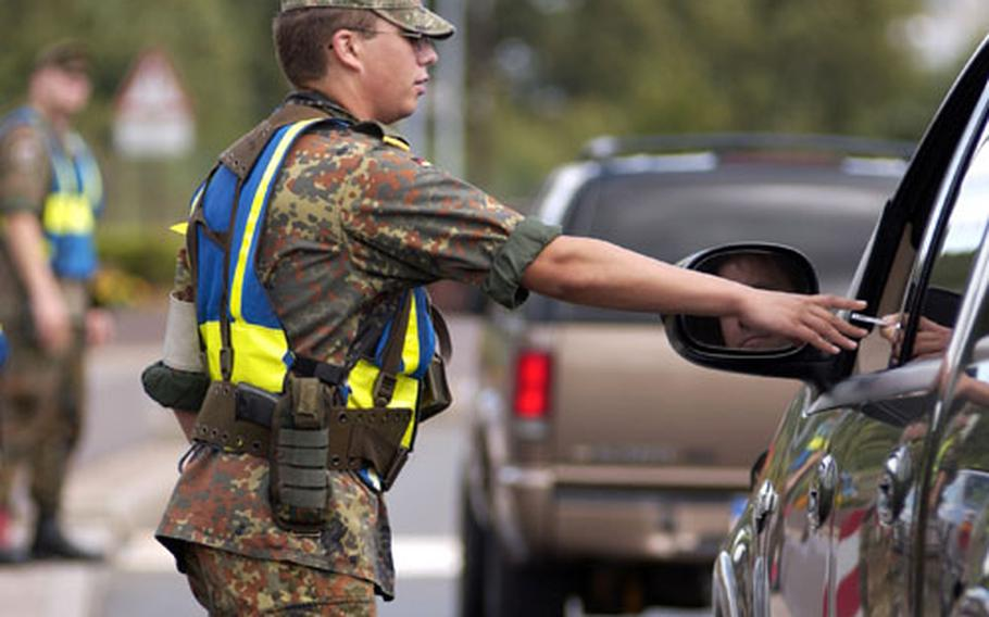 Benjamin Hormann, a member of the German Bundeswehr, checks identification cards at Ramstein Air Base's west gate last month. Before the Sept. 11, 2001, terrorist attacks, most bases in Germany were open to the public.