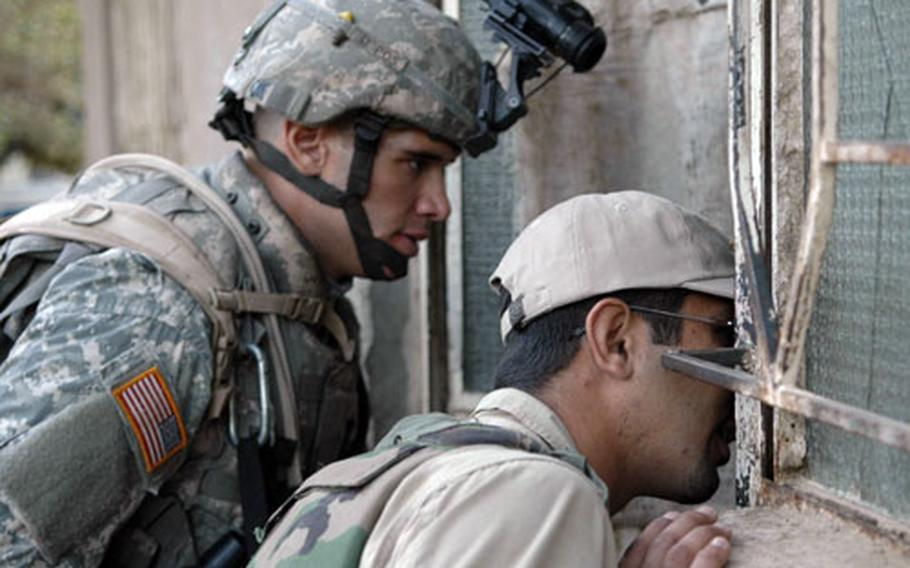 1st Lt. Dave Smart, 25, of Oak Lawn, Ill., and an Iraqi interpreter call to residents in a small village south of Baghdad last week.