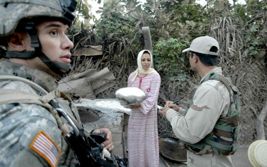 First Lt. Dave Smart and his Iraqi interpreter question an Arab woman Wednesday as she bakes bread outside her home in a small village south of Baghdad.
