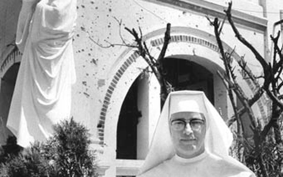 Sister Mary stands in front of the bullet-riddled entrance to the convent and school she oversees near the U.S. air base at Vinh Long