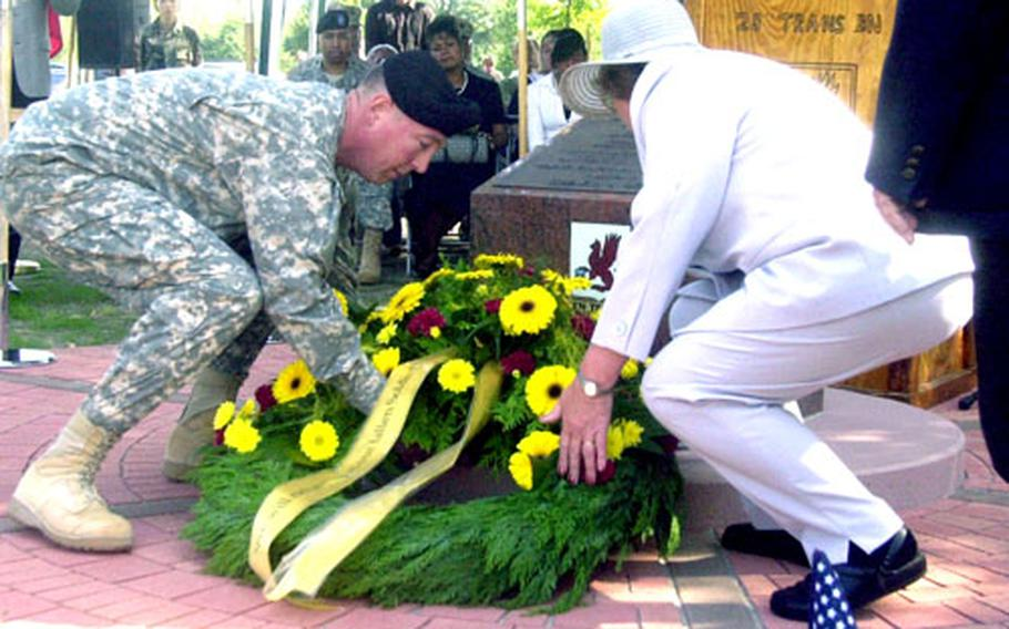 Lt. Col. Stephen E. Farmen, left, 28th Transportation Battalion commander, and Silvia Britz, aunt of the late Sgt. Tatjana Reed, place a wreath Monday on the newly dedicated 28th Transportation Battalion memorial in Mannheim, Germany. Reed, a soldier with the 66th Transportation Company, died July 22, 2004, while serving in Iraq.