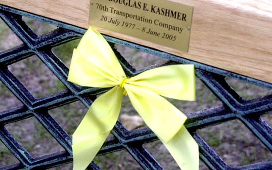 A plaque and ribbon on one of three park benches at the 28th Transportation Battalion Memorial Park in Mannheim, Germany, that memorialize the battalion's three soldiers who have died while serving in Iraq.