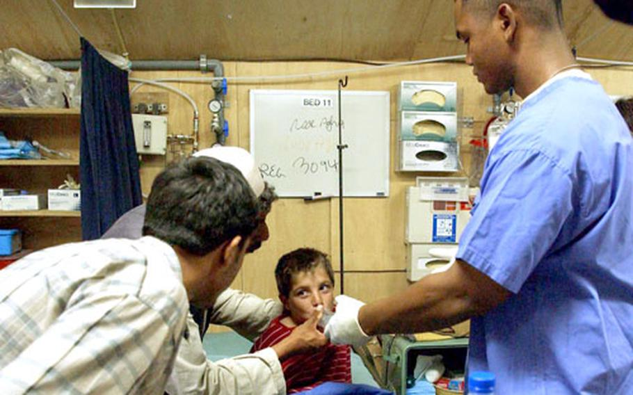 With the help of an interpreter, Sgt. Matthew Younger, right, a respiratory therapist with the 14th Combat Support Hospitalm, shows an Afghan boy and his father how to use an inhalator.