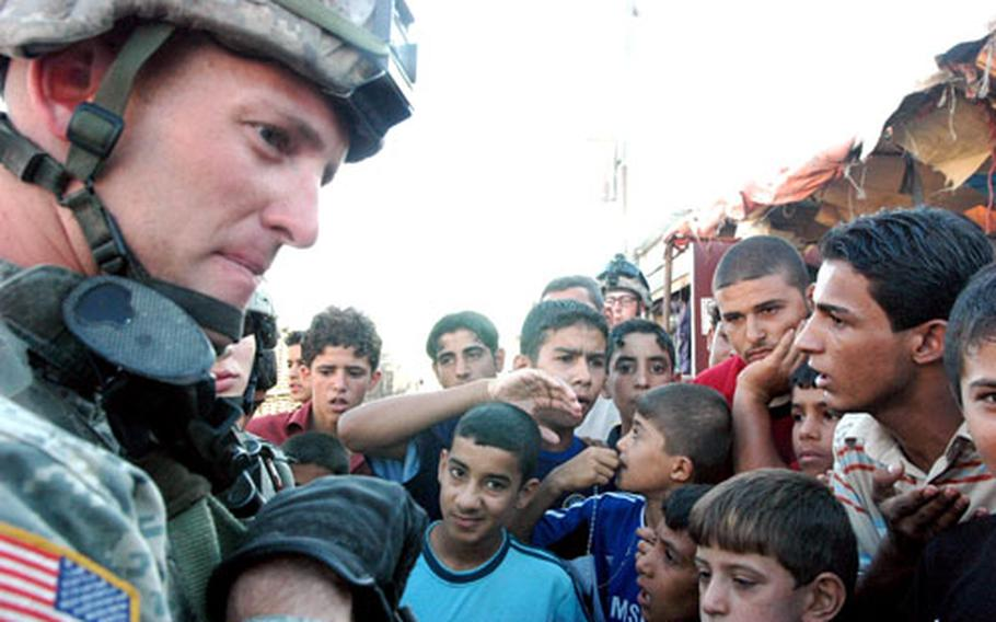 At a market in Sadr City, Baghdad, a crowd of local men and boys gather around Capt. Kevin Sharp, of the 1st Battalion, 17th Infantry Regiment.