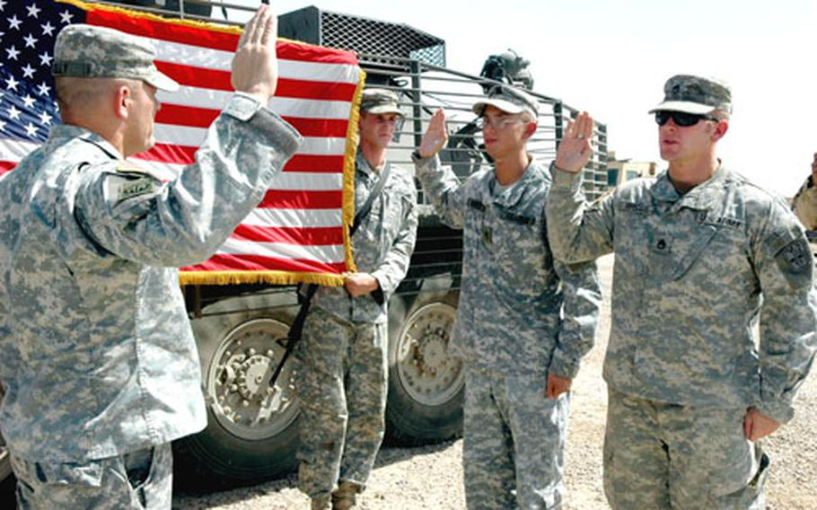 Staff Sgt. Chris Briggs, right, and Staff Sgt. Gilbert Romero, second from right, re-enlist Monday at a ceremony at Camp Taji, Iraq. Their battalion commander, Lt. Col. Al Kelly, left, praised them for re-enlisting even after the unit was extended for another four months in Iraq.