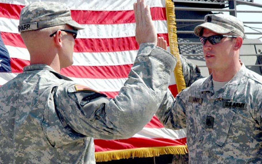 Staff Sgt. Josh Varney, right, re-enlists Monday at a ceremony at Camp Taji, Iraq.
