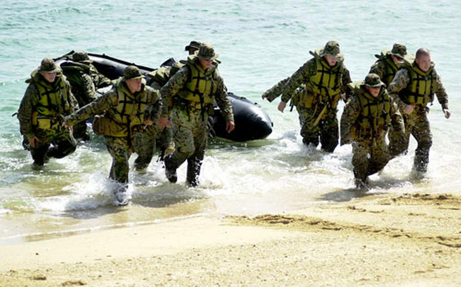 Marines from Alpha Company, Battalion Landing Team 1/5, with the 31st Marine Expeditionary Unit, rush back to shore after helping a boat crew carry their boat to the water during training at Blue Kin, Okinawa.