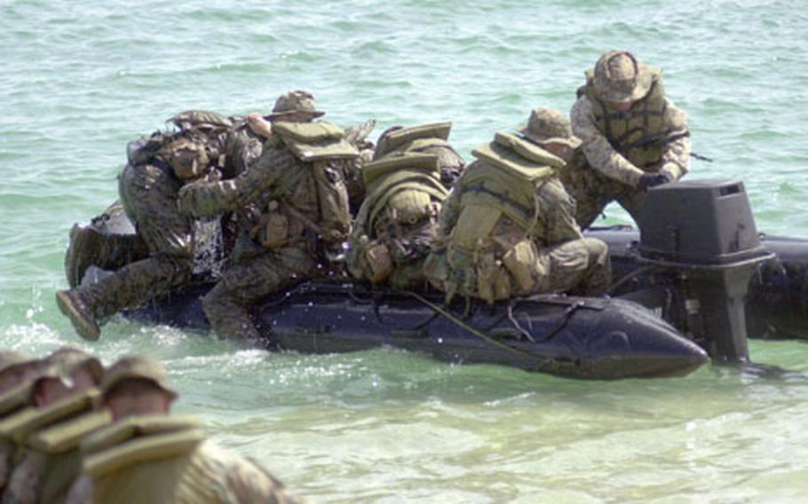 Marines with Alpha Company clamber aboard as a crewman starts the Zodiac boat's engine at Kin Blue Monday.