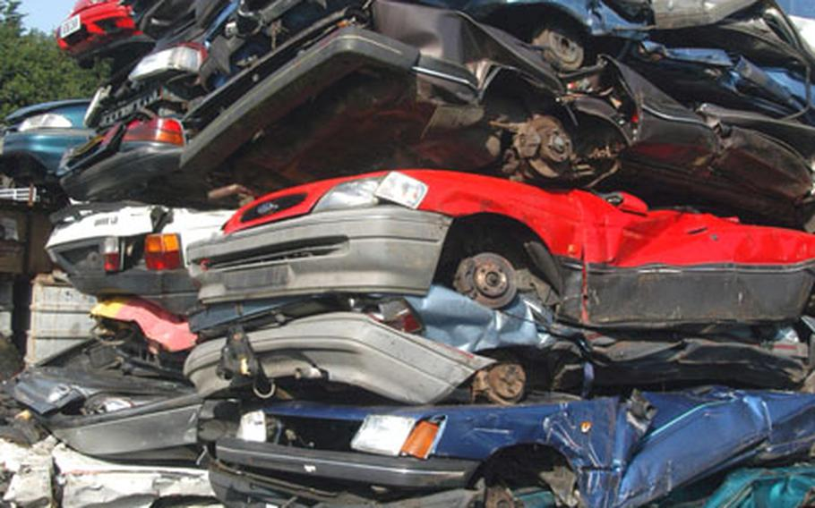 Vehicles, some confiscated by police, are stacked after being crushed at an East Anglian junkyard. Drivers in Suffolk County who have no insurance risk having their cars crushed as part of a program launched Aug. 31 by the Suffolk Constabulary.