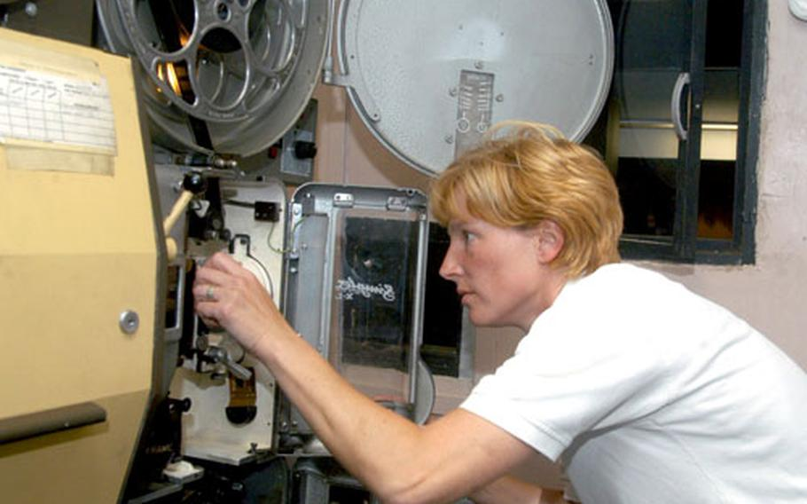 Libby Philpot, one of the supervisors of the RAF Lakenheath movie theater, feeds a film through a projector before a recent showing.
