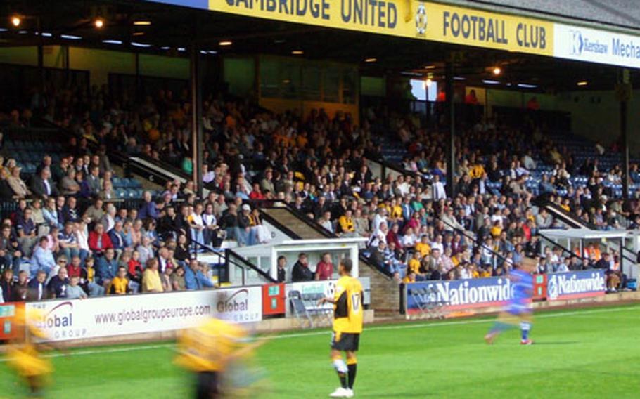Cambridge United Football Club players rush to defend a throw in during a recent game at Abbey Stadium.