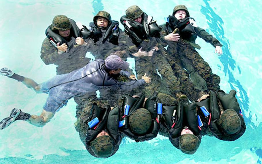 A survival systems instructor demonstrates how a carpet formation can be used to keep injured Marines afloat at the Camp Hansen pool Monday as part of a two-day course on helicopter water egress and survival.