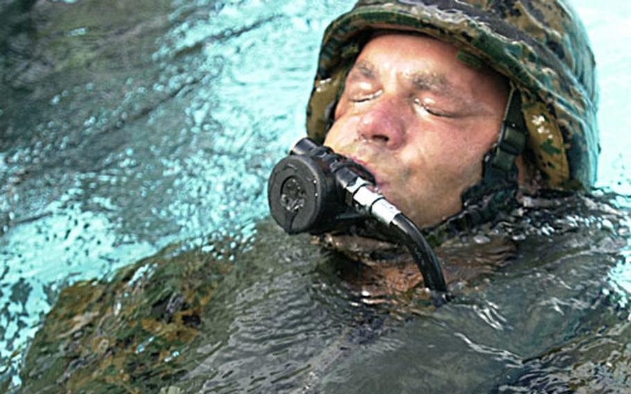 Staff Sgt. Daron Wilkinson practices clearing water out of the mouthpiece of a breathing device while receiving water survival instructions at the Camp Hansen pool.