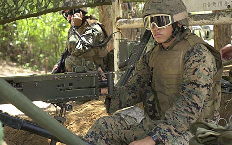 Lance Cpl. Jose Cruz, 20, mans a 50-caliber machine gun and Lance Cpl. Seth Elizalde, 21, monitors the radio at the entry control point to Combat Logistics Battalion 31's base camp at Kin Blue Monday.