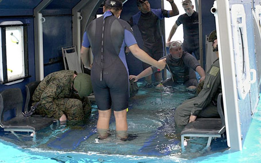 Instructors tell Marines to assume the brace position for ditching as a mock helicopter module enters the water and flips upside down at the Camp Hansen pool on Monday.