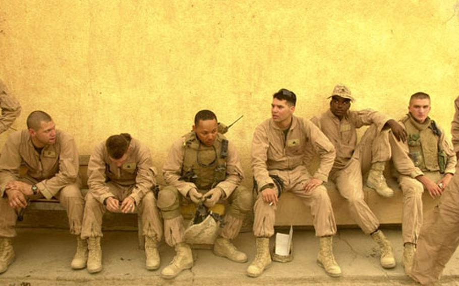 """After what they described as a """"quiet day,"""" Jump Team members relax during a debriefing. From left to right, Cpl. Arvel Rose III, Cpl. Michael Deibert, Navy Petty Officer 2nd Class George """"Doc"""" Grant, Cpl. Mario Huerta, Lance Cpl. Robert Jewell and Lance Cpl. Albert Kiser."""