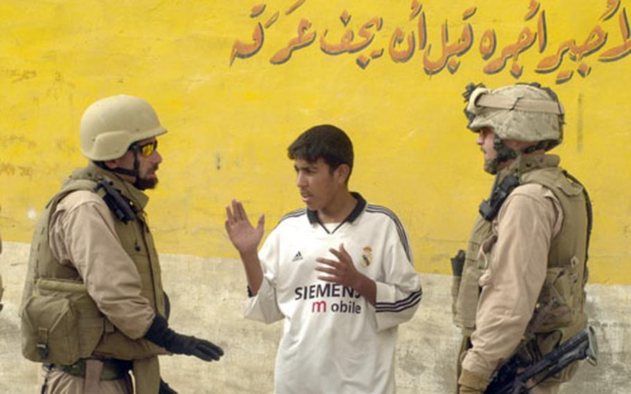 Lt. Col. Todd Desgrosseilliers, right, and a translator question an Iraqi teen after insurgents fired a missile that killed a Marine translator.