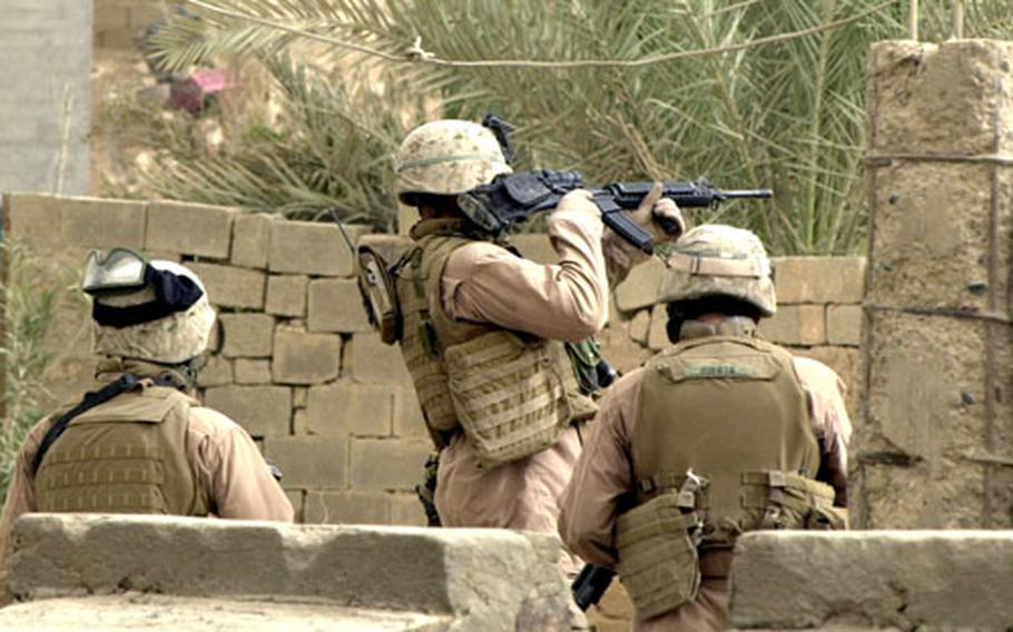 Flanked by Cpl. Mario Huerte, right, and an unidentified Marine on the left, Navy medic Petty Officer 2nd Class George Grant uses his scope to look over a wall for snipers and rocket teams.
