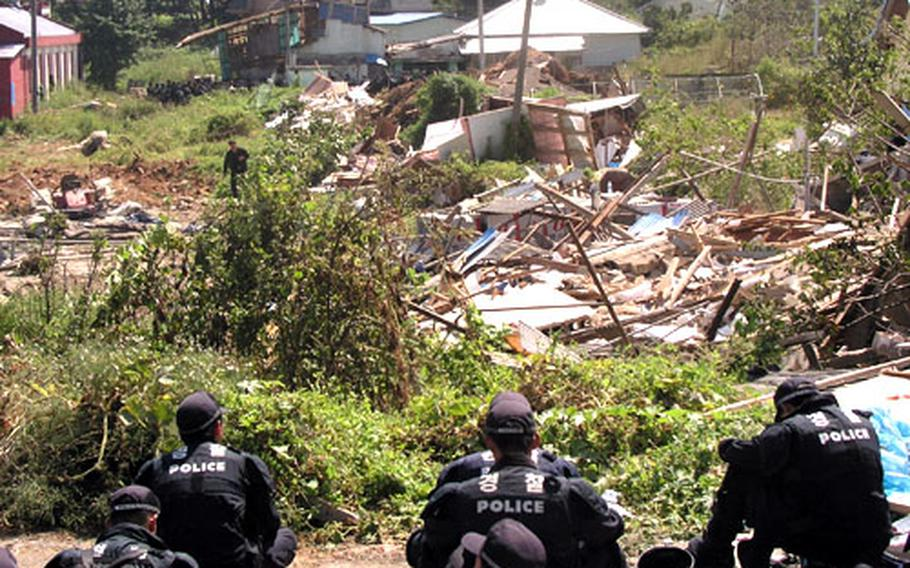Riot police in Daechu-ri village at Pyeongtaek, South Korea, look out on the remains of some of the dozens of vacated homes torn down by work crews Wednesday to help clear the way for Camp Humphreys to expand.