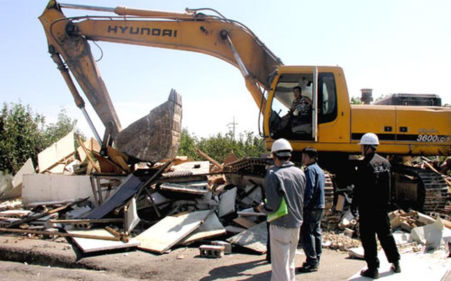 An earthmover demolishes a vacated home.