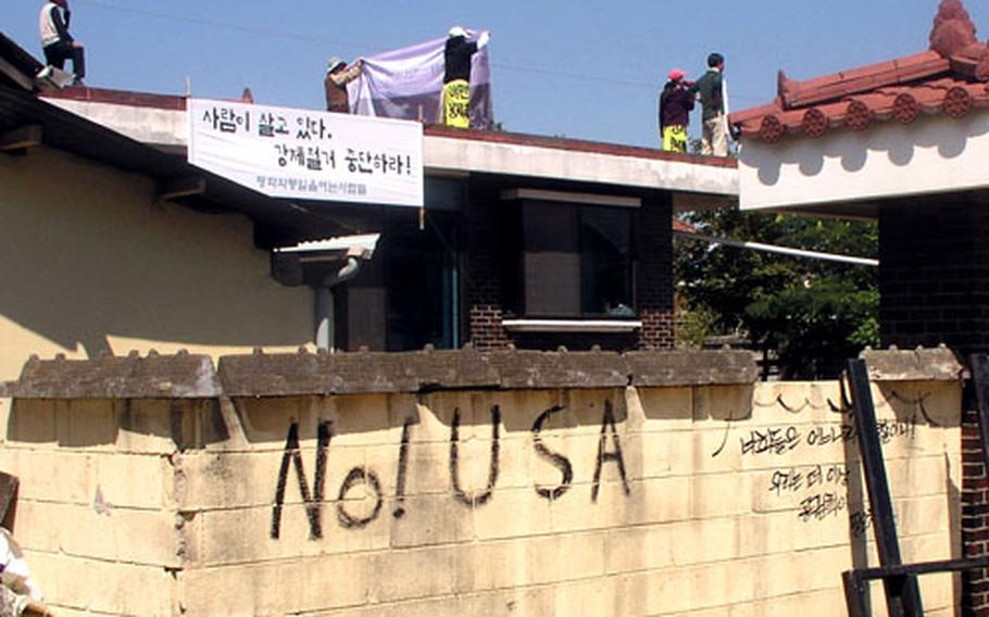 """On the wall of a home in Daechu-ri, the words """"No! USA"""" appear on a wall on Wednesday. Activists on the rooftop are shouting their opposition to the U.S.-South Korean agreement that will see Camp Humphreys expand onto nearby lands."""