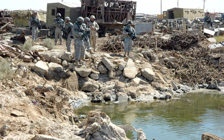 Soldiers from the 1st Battalion, 17th Infantry Regiment, 172nd Stryker Brigade Combat Team examine a lagoon in a junkyard during an operation in Shab on Thursday.
