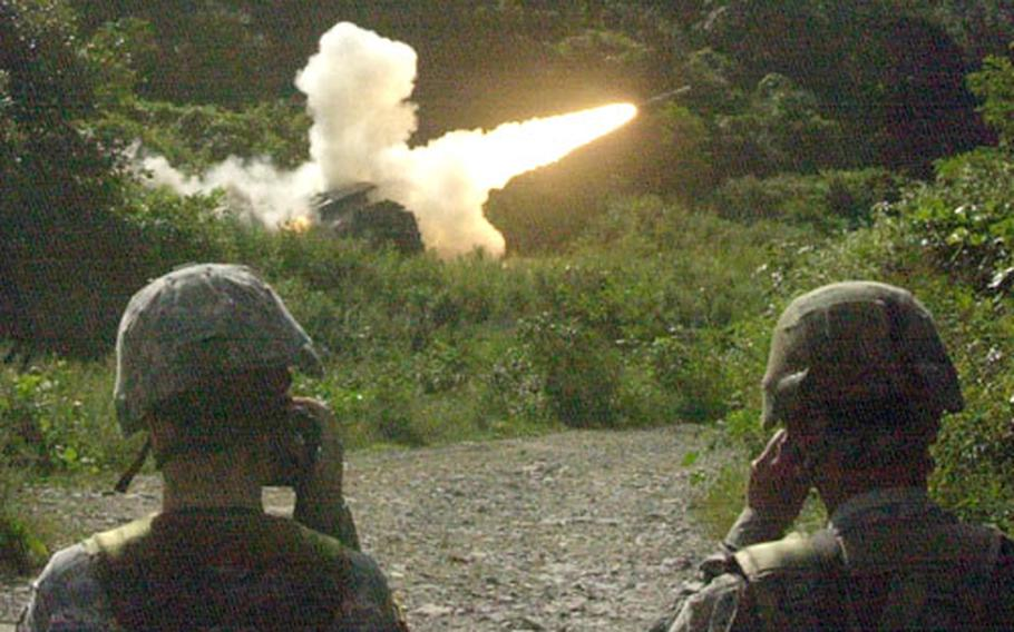"""Soldiers watch as a Multiple Launch Rocket System crew fire a training rocket near the northeastern edge of Gyeonggi province known as """"Rocket Valley"""" Wednesday."""