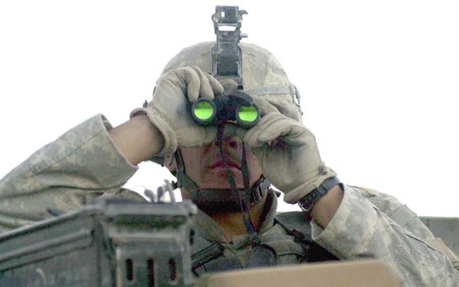 Pfc. Michael Cloutier peers through binoculars as American and Afghan soldiers try to flush out the trigger man of a roadside bomb that destroyed a Humvee on the first day of Operation Mountain Fury in Ghazni province, Afghanistan. No one was injured in the explosion.