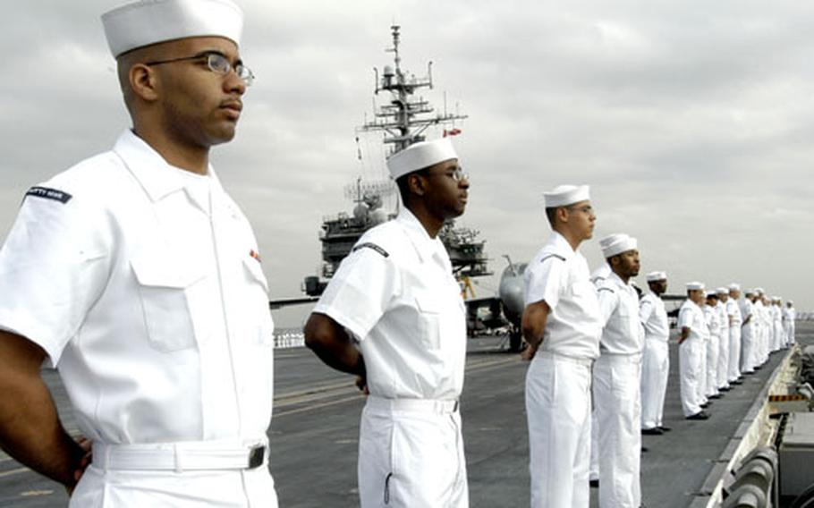 USS Kitty Hawk sailors man the rails as the ship steams into Truman Bay, Yokosuka, Japan, after completing a 99-day summer underway period.