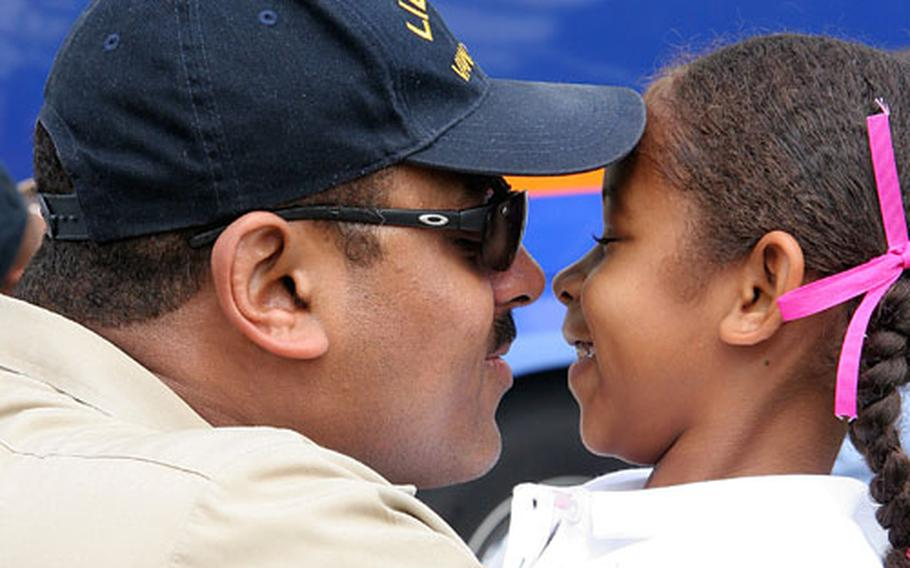 Chief Aviation Electronics Technician Gregory McDaniel of Airborne Early Warning Squadron 115 is greeted with a hug and kiss from his daughter upon his return home Friday to Naval Air Facility Atsugi, Japan, after a routine three-month deployment aboard USS Kitty Hawk.