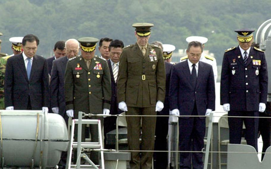 Marine Maj. Gen. Duane Thiessen, center, and South Korean officials bow in silence after laying the memorial wreath in the ocean during the Inchon landing commemoration ceremony.