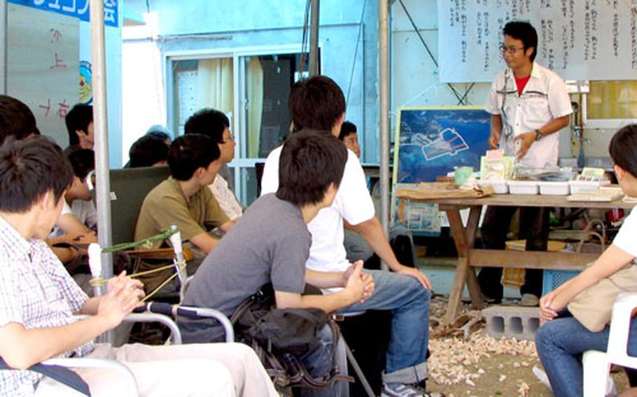Shin Tomita, an antibase activist, briefs a group of college students from Tokyu University and Hitotsu Bashi University on his group's opposition to construction of a new Marine air station on Camp Schwab. Some 30 protesters staged a sit-in at the camp's main gate on Friday.