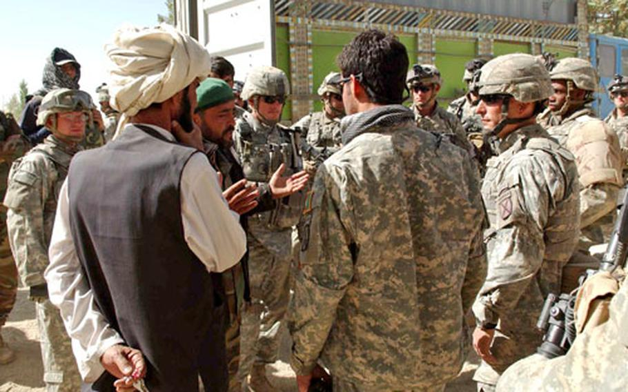 Lt. Col. Chris Toner, at right center, 2nd Battalion, 87th Infantry Regiment, listens to an Afghan National Army commander following a disagreement between Afghan army and Afghan National Police in Miri on Saturday.