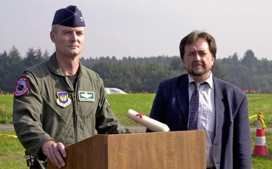 Air Force Col. Darryl Roberson, left, commander of the 52nd Fighter Wing at Spangdahlem Air Base, and Bernhard Schaefer, wing community relations adviser, listen to reporters' questions Saturday while standing in front of the site where an F-16 crashed Thursday.