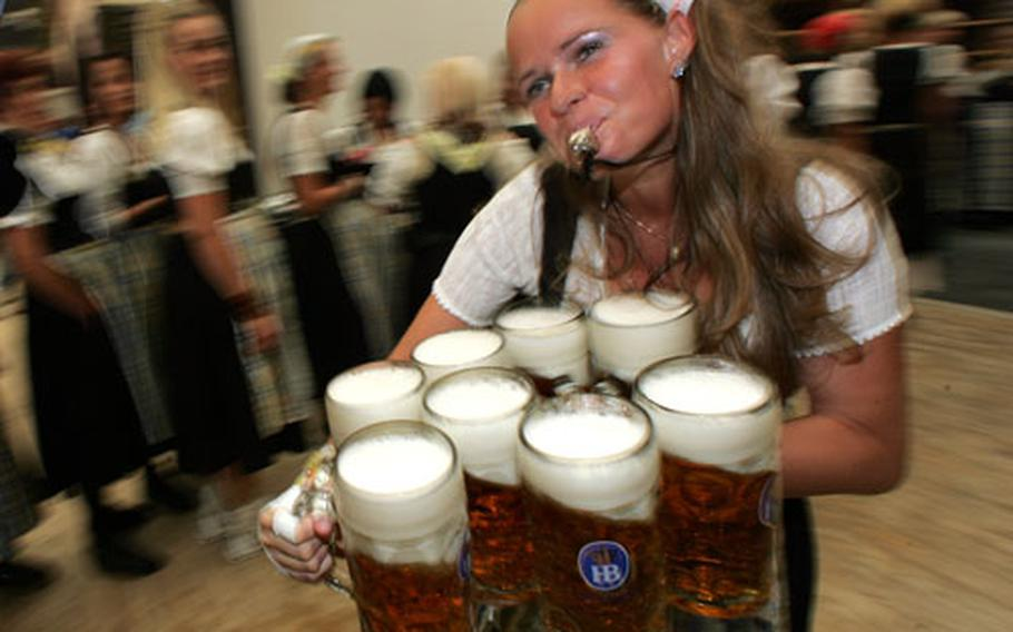 A waitress carries a load of beer mugs as she whistles her way through the crowd at the start of the Oktoberfest beer festival in Munich, Germany. The world's biggest beer festival opened on Saturday.