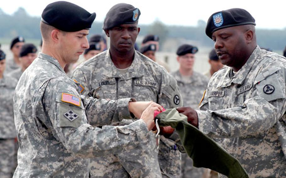 Capt. Douglas M. Sweet, left, commander of the 596th Maintenance Company, and company 1st Sgt. Darrold Harper case the company's guidon as Spc. Richard Louis, center, holds the staff Friday during a farewell ceremony in Griesheim, Germany. The unit, based in Darmstadt, leaves for its second Iraq deployment in the next few days.