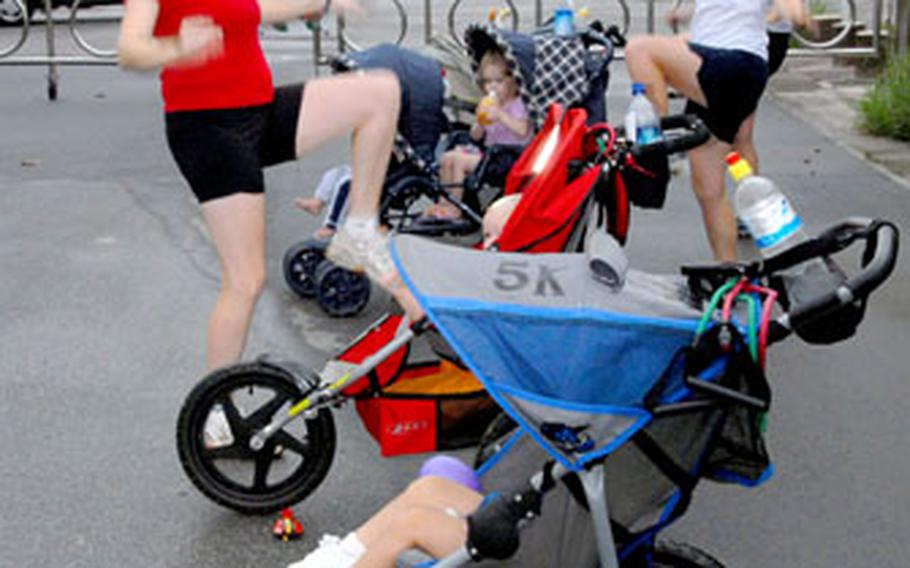 Participants in Stroller Strides do warm-up exercises Thursday in a circle of strollers before heading out on a power walk peppered with body-toning intervals using resistance bands. Mothers meet at Kadena Air Base, Okinawa, to exercise together with their children.
