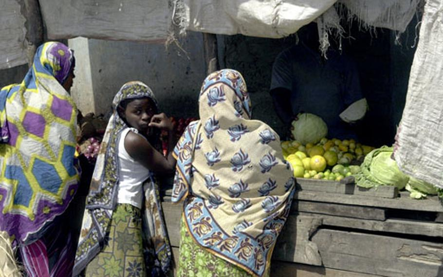 Young women bargain for vegetables at a market in one of Dar es Salaam, Tanzania's poorest districts.