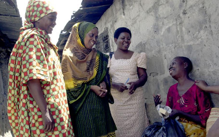 Members of TANHOPE — an organization that performs development and charity work in Dar es Salaam — give donations to Fortunata Simon, a 30-year-old woman suffering from AIDS. Simon moved her five children to a slum in Dar when she was no longer able to work in her village.