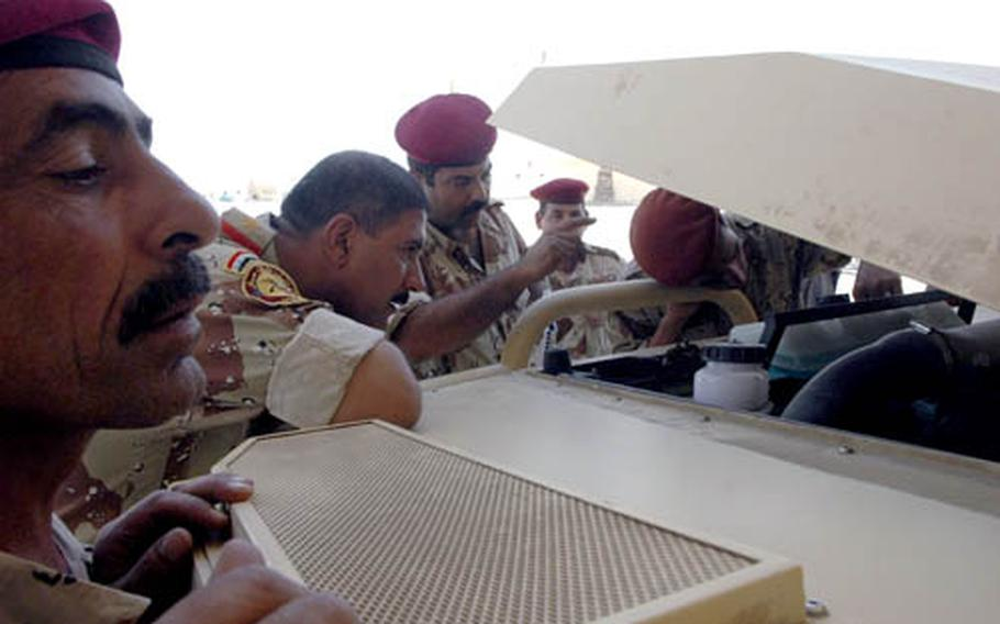 Iraqi army officers peer under the hood of a new, Polish-built armored car in Najaf, Iraq, recently.