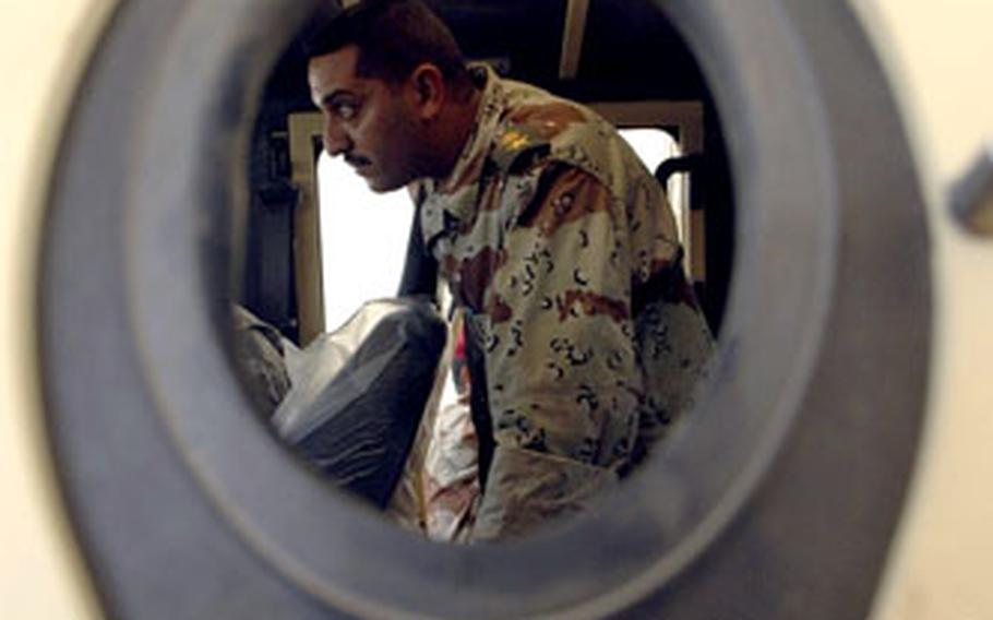 An Iraqi army captain can be seen inspecting the interior of an new Polish-made armored through one of the vehicle's gun ports recently.